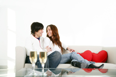 Let your property with Ian Gibbs Letting Agents in Enfield - Couple on sofa with champagne glasses